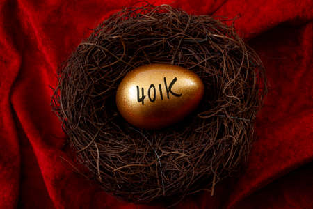 Individual retirement account, personal savings and pension fund concept with close up on a gold egg in a nest symbolizing the accumulated wealth with the text 401k, isolated on red velvet background