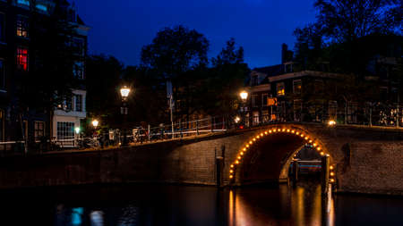 Dutch landmarks and travel destinations in the Nederlands concept with a bridge over a canal in Amsterdam illuminated by light bulbs at night