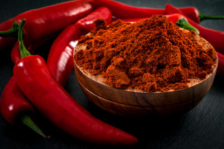 Mexican cuisine and spicy food concept with close up on fine ground red pepper powder in a wooden bowl surrounded by a bunch of hot chilli peppers on a dark background with dramatic light