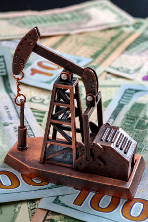 The importance of the petrodollar in the american economy and drilling for oil and profits concept with a oil derrick on top of US dollar bills or notes Banco de Imagens