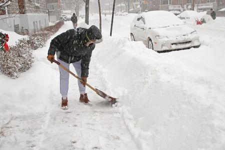 Woman shoveling after a snow storm. Canada.