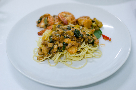 Delicious spaghetti with shrimps and basil on a white plate and white background.