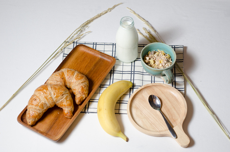 Breakfast table with Croissant and Muesli and banana and fresh milk give vitamins, minerals, carbohydrates, fats, oils, protein.