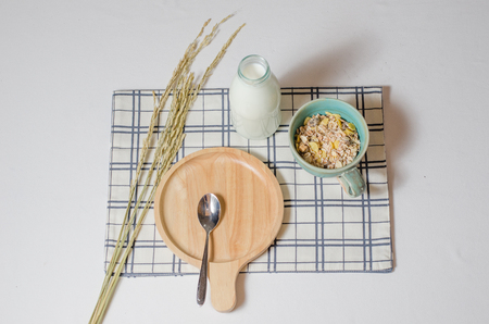 Breakfast with  Muesli and fresh milk and nice wooden plate and spoon Stock Photo