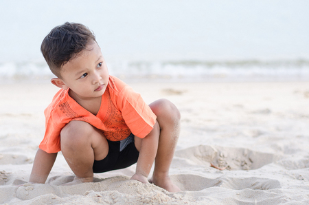 Boy, about 4-5 years old, playing white sand on beach alone with sadness. Stock Photo