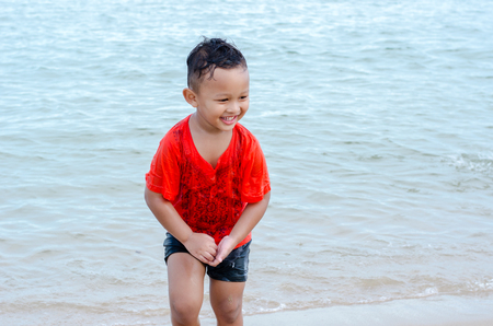 Happy little boy on vacation having fun swimming on beach Stock Photo