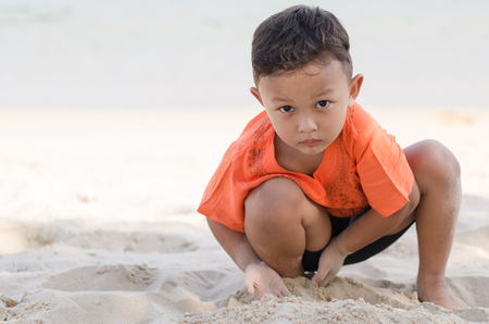 Asian Happy little boy 4-5 year on vacation having fun playing sand on beach