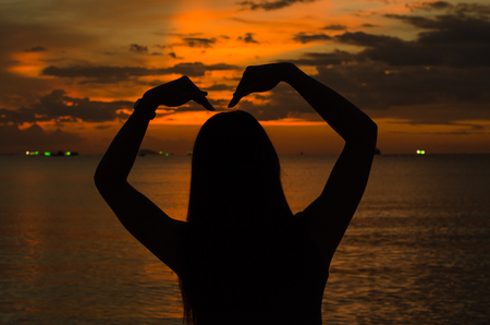 Silhouette of asian woman making sign of heart alone on beach with the sunlight when sunset. Stock Photo