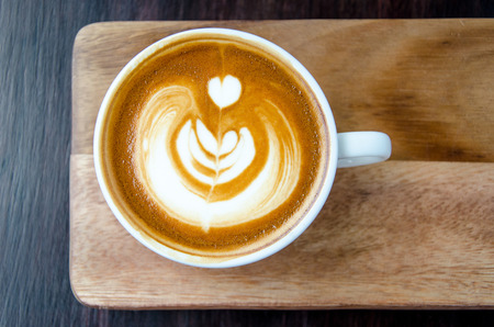 Cup of coffee with beautiful Latte art on wood plate with black background. Stock Photo