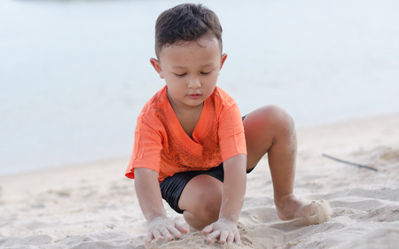 Asian Happy little boy 4-5 year on vacation having fun on beach