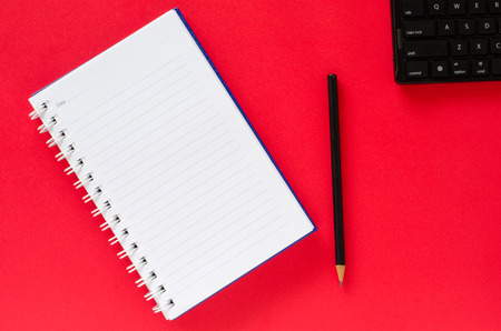 White note book and black pencil and black keyboard on red color background with copy space. Stock Photo
