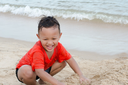 Happy little Asian boy 4-5 year old on vacation having fun on beach and playing sand Stock Photo