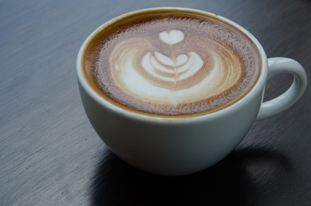 White cup of coffee with beautiful Latte art on black background. Stock Photo