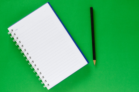White note book and black pencil on green color background with copy space. Stock Photo