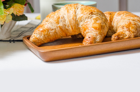 Breakfast with Croissant on wooden board in white background on the table