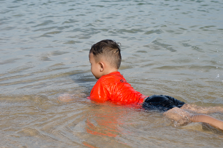 Asian Happy little boy 4-5 year old on vacation having fun swimming on beach