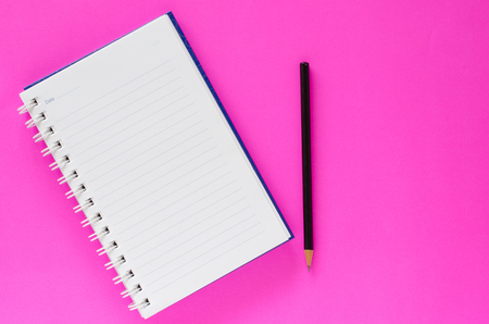 White note book and black pencil on pink color background with copy space.