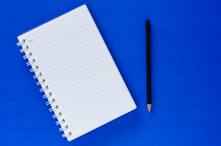 White note book and black pencil on blue color background with copy space.