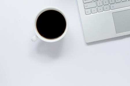 Laptop and black coffee on white background with copy space.