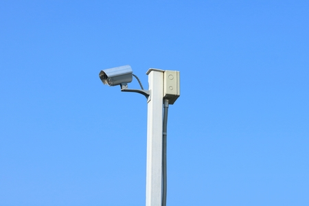 Closed circuit television camera on white steel pole with the background of blue sky.