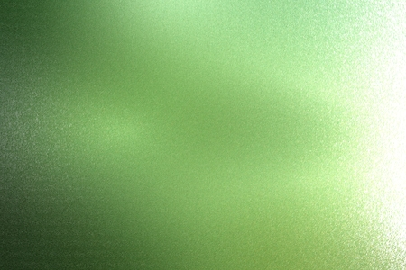 Light shining on rough dark green metallic wall texture, abstract background Imagens