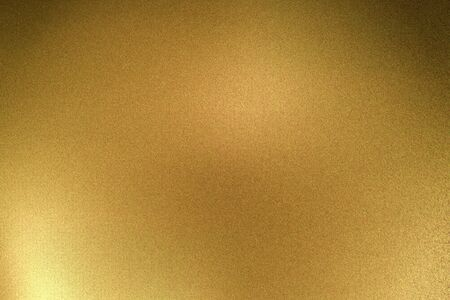 Light shining on gold metallic plate in dark room, abstract texture background