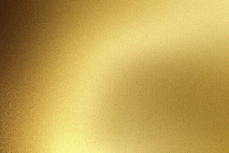 Light shining on gold wave metal plate in dark room, abstract texture background