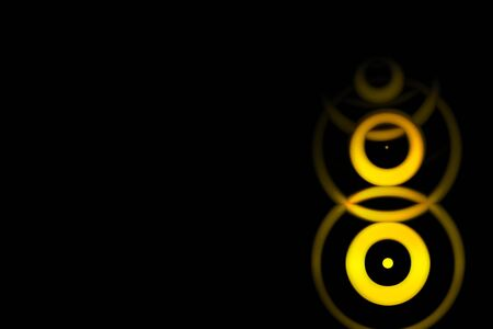 Abstract yellow sound waves oscillating with circle ring on black background Фото со стока