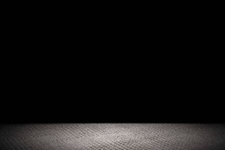Light shining down on rough gray concrete floor in dark room with copy space, abstract background