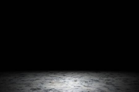 Light shining down on dirt gray marble floor in dark room with copy space, abstract background