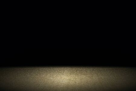 Light shining down on brown carpet floor in dark room with copy space, abstract background