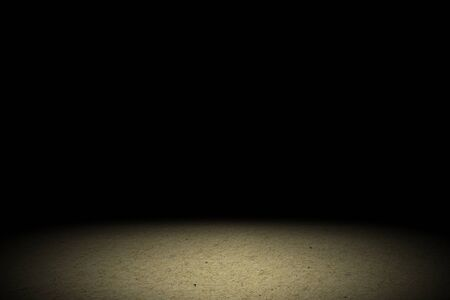 Light shining down on brown soil floor in dark room with copy space, abstract background Imagens
