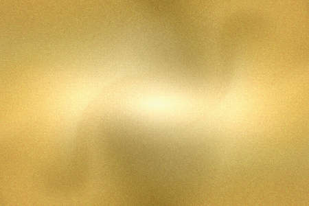 Light shining down on gold foil metallic wall, abstract texture background