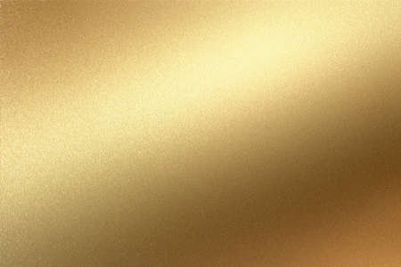 Glowing gold foil metal panel wall with copy space, abstract texture background