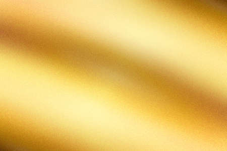 Light shining on gold painted metallic wall with copy space, abstract texture background