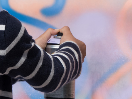Young boy artist using spray wall graffiti background 写真素材