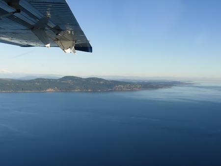 Wing plane blue sky flying above ocean copy space