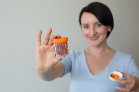 Attractive female doctor  shallow depth of field hand holding orange medicines Stock Photo