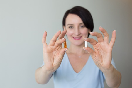 Female portrait vertical shot hand holding orange pills