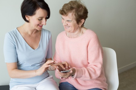 Young woman helping elderly female using smartphone Stock Photo