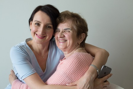 Elderly mother hugging adult daughter concept affection Stock Photo