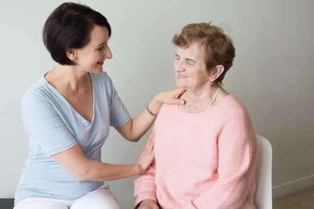 Young female holding hand on shoulder of elderly woman Stock Photo