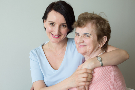 Elderly mother with adult daughter hugging portrait Stock Photo
