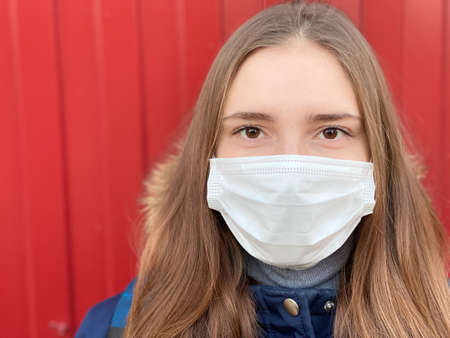 Attractive teenage girl wearing medical mask outdoor copy space