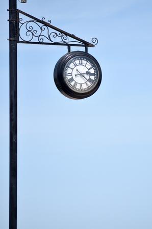 City clock on an iron pillar against a blue sky with Roman numerals.