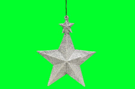 Christmas and New Year's silver five-pointed star  on the green isolated background. The toy of old times. Stock Photo