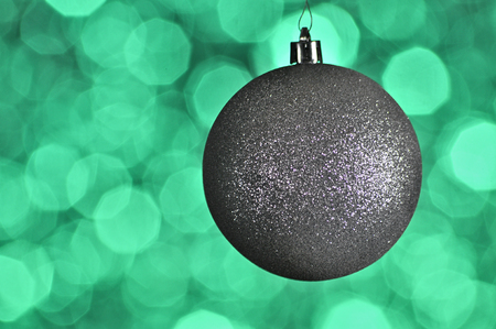 Elegant colored New Year and Christmas ball on the background with light effect and bokeh.Turquoise,green,silver