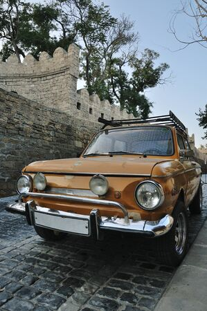 Old car of yellow color on the street of the Old Town of Baku