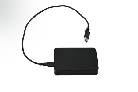 Portable hard drive for backing up various files on an isolated white background