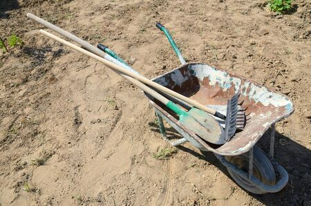 Wheelbarrow with a shovel, rake and shovel for housekeeping and construction work,on site.